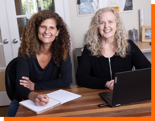 myCEO.ca business coaches Glorie Averbach and Betty Hasker seated at a desk